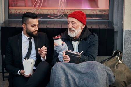 Young beardy man in suit sitting with beggar on floor on street and give cup of coffee. Different segments of society, social inequality