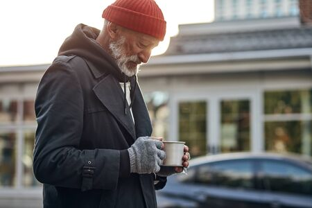 Penniless man collect money for shelter, food. Male desperately look at empty cup from coffee. Life depends on money. Homeless person on street Banco de Imagens