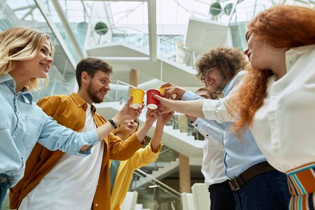 Bottom shot of creative talented designers, holding colourful paper cups with juice, clinking glasses, have load toothy smile, spending happy time at work