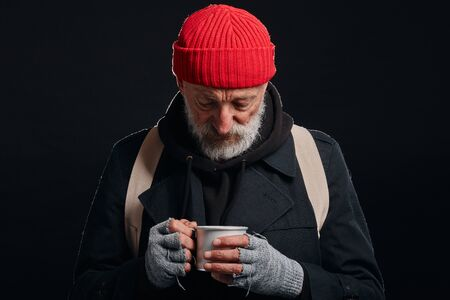 Tired and sick homeless male in coat and red hat look with sadness at mug. Portrait of bearded man isolated over black background Banco de Imagens