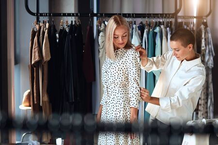 Modern caucasian designer happily takes measurements of young female in room. Background clothes