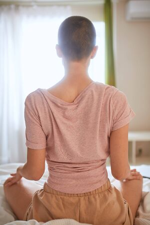 Back view of woman in t-shirt doing yoga exercise on bed in light room. Sit in pose lotus, meditating