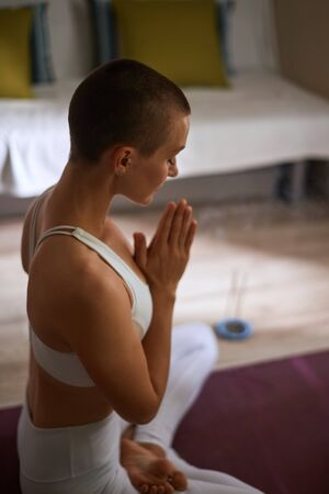 Woman meditating indoors. Attractive and short-haired caucasian model in white sportclothes sitting on mat and practice yoga with candles. Pray