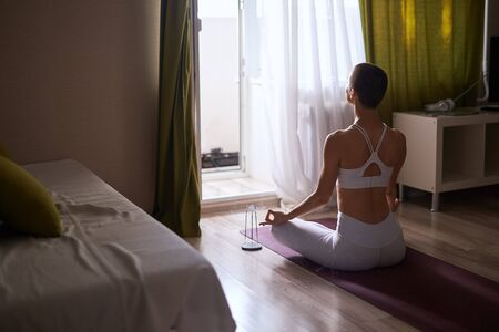 Woman sitting on purple mat in lotus pose towards the window. Dressed in white sportswear. Yoga at home as hobby