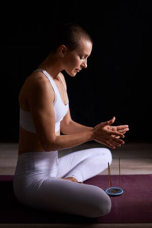 Meditating woman use aroma stick when meditating and practicing yoga at home in black room. Short-haired and fit female yogi in white sportswear Stock fotó