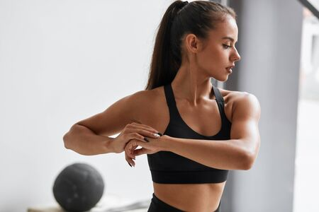 Side view of caucasian attractive girl stretch muscles at white gym im black topic. Window background. Side view