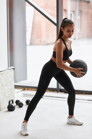 Attractive flexible girl limbering holding ball. Female in black leggins and topic in gym. Window background