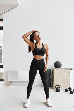 Caucasian long-haired girl in black leggins and topic stretching body, arms. White gym background