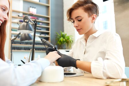 Beautiful manicurist doing work in beauty salon. Redhead caucasian girl sit in manicure procedure. Side view