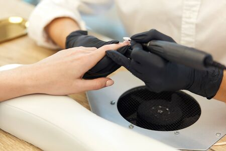 Manicurist in black gloves do mechanical manicure of nails. Closeup of beautiful female hands. clean and sterile