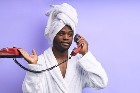 African man in bathrobe and towel talk on landline telephone isolated over purple background