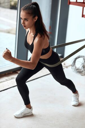 Attractive sporty cross fit female exercises in light isolated studio. Using elastic rope, ribbon. Dressed in black sportswear. WIndow background