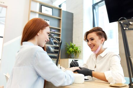 cheerful open-minded manicurist in white clothes make manicure to young caucasian woman with red hair in shirt, Background beauty salon Banco de Imagens