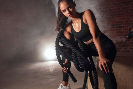 Young sporty female sit in gym holding battle rope. Crossfit, sport, healthy lifestyle concept Standard-Bild - 133414468