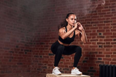 Beautiful caucasian woman in black jump doing squats on fit box. Sport, healthy lifestyle concept. Brickwall background.