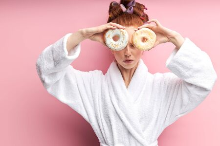 Cute redhaired woman holding sweet donut, happy after shower in bathrobe and curlers on hair, closed both eyes. Isolated over pink background 版權商用圖片