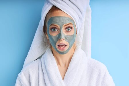 Portrait of young girl with mask for face skin. Isolated over blue background