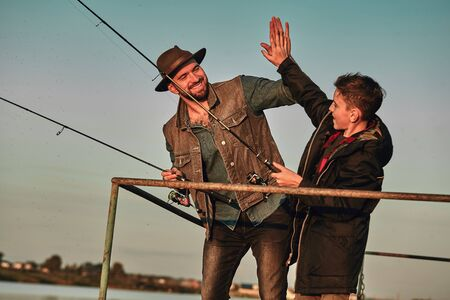 Father and son stand on pier. They fish and give each other five