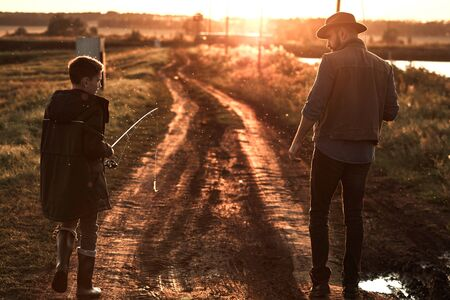 Father and son walk along country road along lake to fishing spot. Sunset. Stockfoto