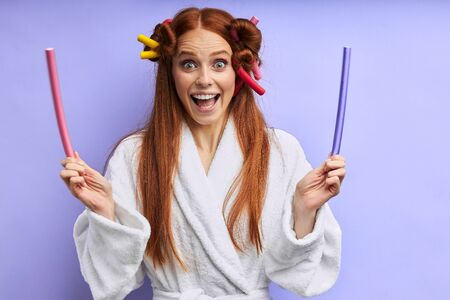 Young caucasian woman in bathrobe with curlers on hair posing, look at camera. Portrait, isolated over purple background