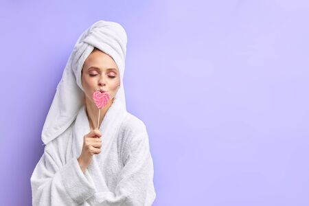 Beautiful caucasian girl holding lollipop, wearing bathrobe and towel. Isolated over purple background