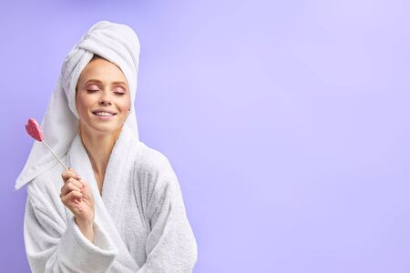 Attractive girl holding lollipop, wearing bathrobe and towel. Closed eyes, Isolated over purple background