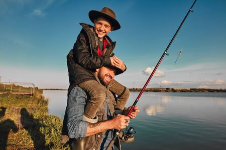 Son and father have fun while fishing. Father holds son on shoulders. Boy hold head. They smile. Background lake. Reklamní fotografie