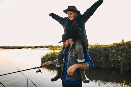 Father and son have fun while fishing. Teen boy happy and smile, sit on father shoulders and raised hands to sides. Reklamní fotografie