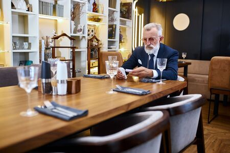 Portrait senior bearded man grey haired in suite sit in restaurant looking electronic cigarette. Modern technologies.