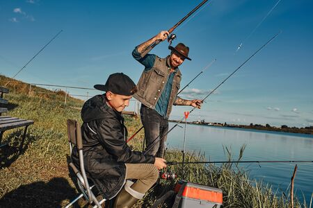 Caucasian father and son fishing near lake together. This is first experience for them. Boy little nervous, father explains and supports.