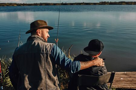 Backs of father and son sit near lake on fishing chairs. Father holds son shoulder and look at him. Reklamní fotografie