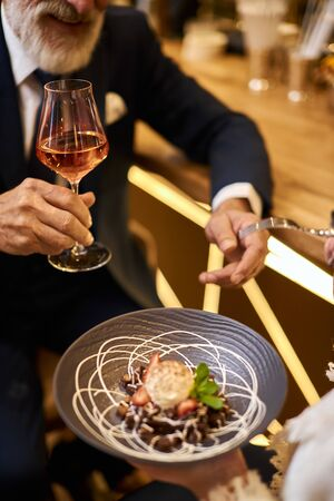 Close image of hand with glass of champagne, sweet dessert on grey dish. Beared man in tuxedo drinking