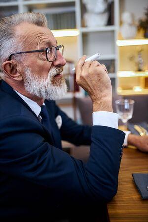 Handsome senior man with glasses smoking electronic cigarette, modern technologies nowadays, stop smoke