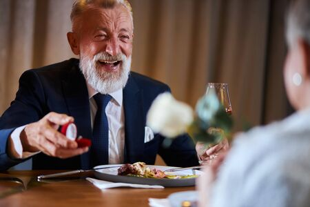Senior man happily looks at woman waiting answer for marriage proposing. Elegant male in suit smile holding a ring, woman hold white rose. Love, relationship concept