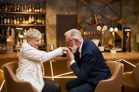Handsome man in beautiful tuxedo and woman in white blazer sit in expensive beautiful restaurant. Male kissing hand and declare his love. Romantic image, light view Imagens