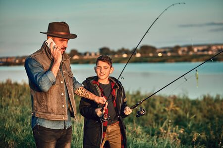 Father and son go fishing. Father takes urgent phone call and gives fishing rod to son 免版税图像