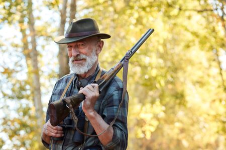 Happy senior hunter smile after getting good, big trophy in forest. Hunting on wild animals, birds. Satisfied hunter with grey beard, holding shotgun on shoulder 스톡 콘텐츠