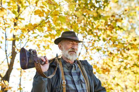 Tired hunter man carrying shotgun on shoulders, look away. Nature background