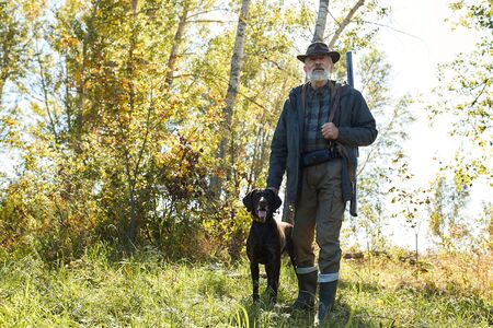 Senior hunter and his dog in forest, look for prey, hunting on wild animals. Hunting season