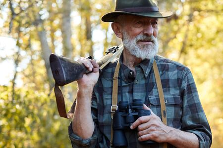Satisfied man with grey beard look away, stand holding binoculars in one hand, shotgun on shoulders. Forest,autumn trees background, sunny day