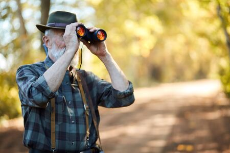 Using binoculars for better hunting on birds. Senior man holding binoculars during hunting in autumn forest. Road background
