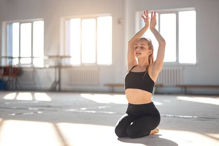 Young flexible woman sits on knees, raises hands up, stretches and trains in brightly lighted class, rhythmic gymnastics