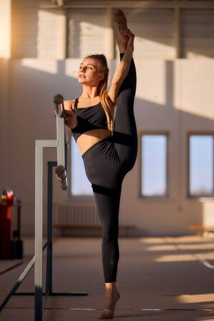 Graceful young art gymnast stands on tiptoe near big window, raises leg up intensively, looks away with confident expression, keeps hand on ballet bar, full lengh, professional sport concept Banco de Imagens