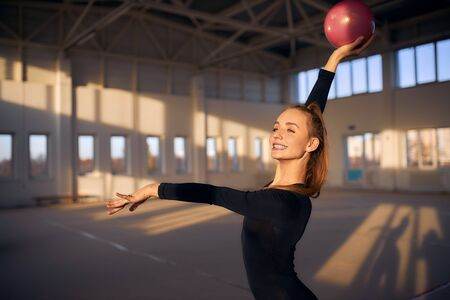 Young female gymnast training with red ball in sports hall, looking away with teeth smile, stretching hand ahead, portrait, professional sport concept