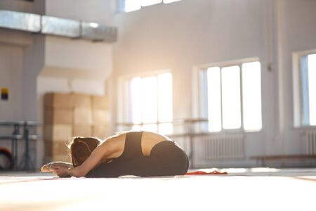 Flexible young girl in black bodysuits sits on floor, gives a stretch,, practicing in modern yoga studio