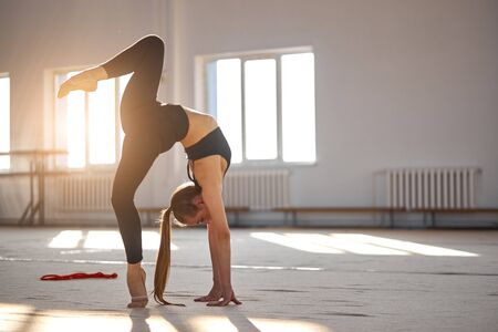Attractive fit woman wears black leggins and bra, standing in bridge pose on one leg, on tiptoe,sport and success concept