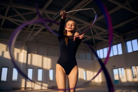portrait of young gymnasts training with colourful long ribbon in dark lighted sports hall, professional sport concept 版權商用圖片
