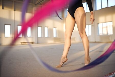 Long beautiful legs of talented art gymnast standing on tiptoe in the middle of brightly lighted sports hall, training with ribbon, close up, indoor shot