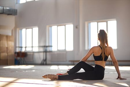 Graceful fit woman wears black sportswear, sits on floor of brightly lighted studio with back to camera, health life concept Imagens