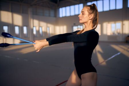 Portrait of young beautiful girl in black leotard, stretching hands with blue clubs ahead, looking aside, background of dark lighted sports hall, gymnastics concept